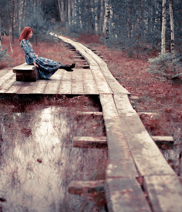 young woman sits on wooden pathway across a tree lined lake